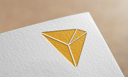 Golden Tron Coin Symbol Write Paper. Tron Coin Logo. Фото со стока