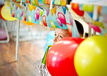 Little boy peeping from under table at party Stock Photo - 12941096