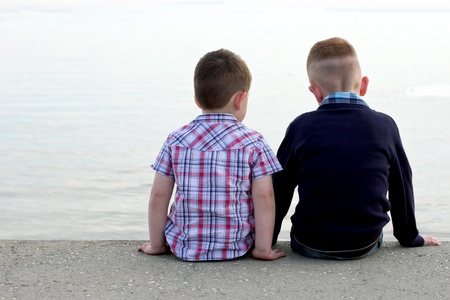 looking behind: two btothers sitting on a beach wall Stock Photo