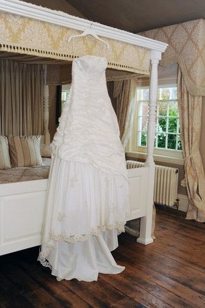 wedding dress hanging in reception room Stock Photo