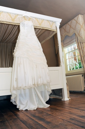four poster bed: wedding dress hanging in reception room Stock Photo