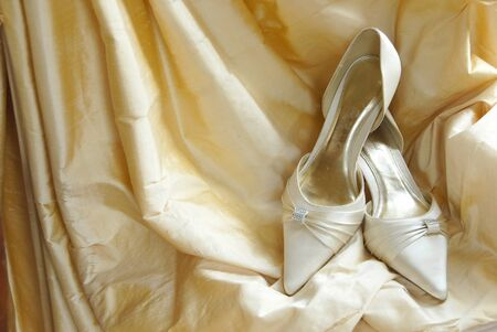 gold coloured wedding shoes on a golden fabric