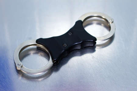 Police style handcuffs on a metal surface Stock Photo - 14341482