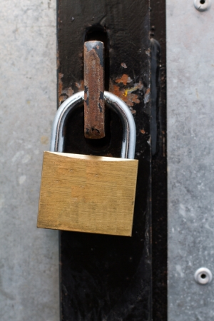 towerblock: a brass padlock securing an iron door together Stock Photo