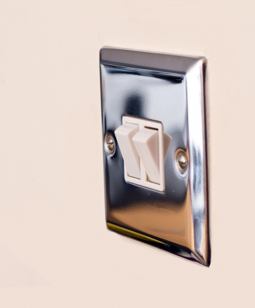 Chrome light switch on a magnolia wall