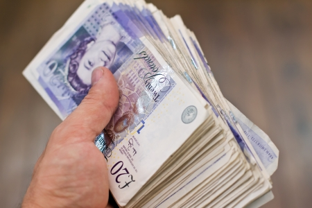 money pounds: a large bundle of british twenty pound notes in the hand Stock Photo