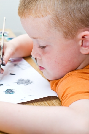 young boy painting a picture with a paintbrush Stock Photo - 14482051