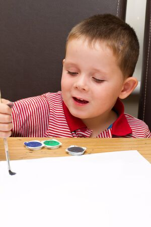 young boy painting a picture with a paintbrush Stock Photo - 14482045