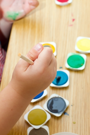young boy painting a picture with a paintbrush Stock Photo - 14472329
