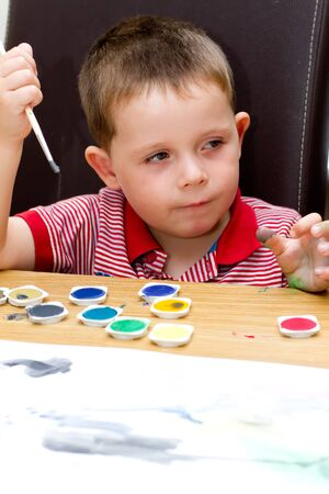 young boy painting a picture with a paintbrush Stock Photo - 14482056