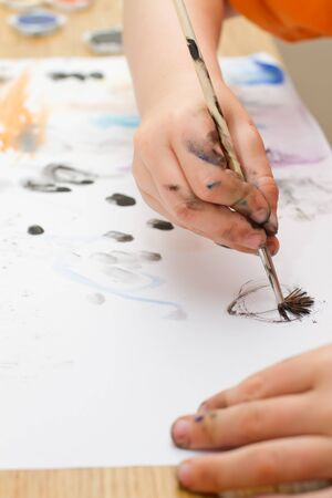 young boy painting a picture with a paintbrush Stock Photo - 14472314