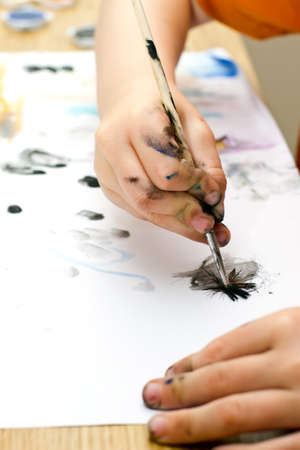young boy painting a picture with a paintbrush photo
