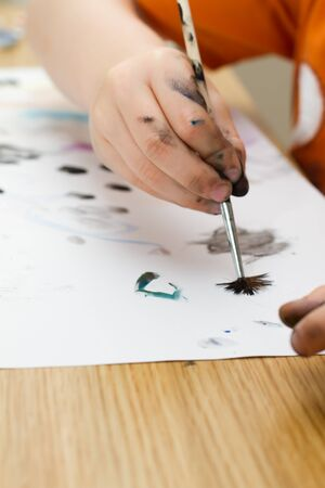 young boy painting a picture with a paintbrush Stock Photo - 14472306