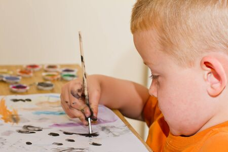 young boy painting a picture with a paintbrush Stock Photo - 14482057
