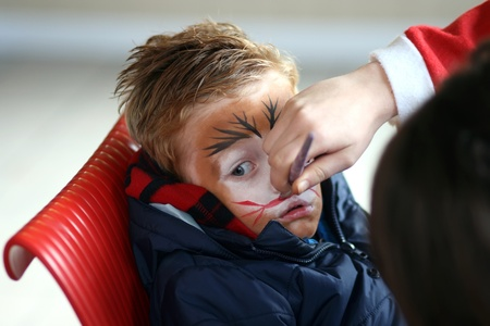 little boy having his face painted like a tiger photo