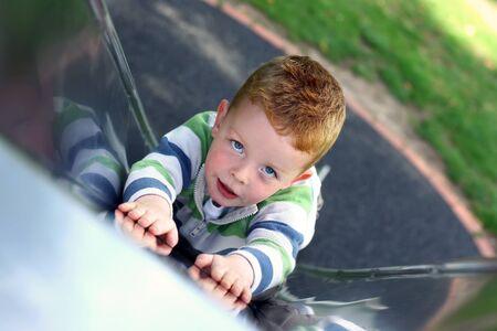 little boy slding down the slide at the park Stock Photo - 15003155