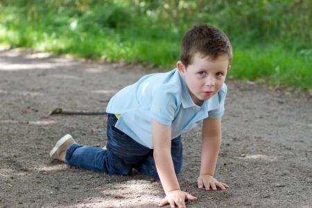 bebe gateando: ni�o peque�o arrastr�ndose a lo largo de un sendero en el bosque Foto de archivo