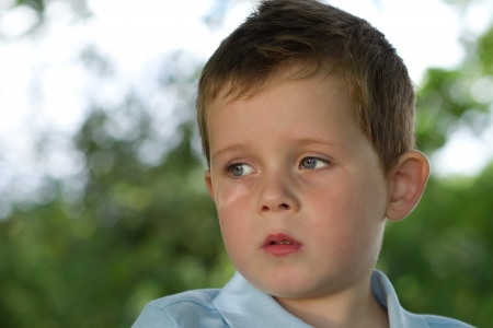 children sad: little boy looking to his right in countryside Stock Photo