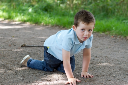 little boy crawling along a woodland path Stock Photo