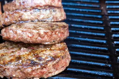 Beef quarterpounder burgers begin to cook on the gas barbecue Stock Photo - 15084376