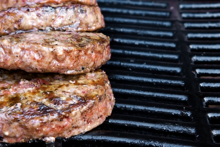 Beef quarterpounder burgers begin to cook on the gas barbecue