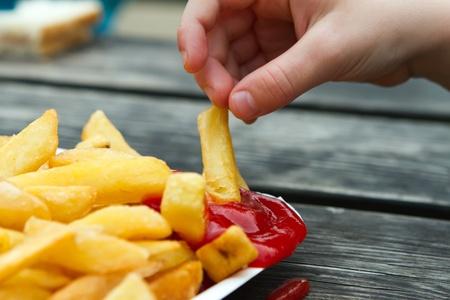 comida inglesa: ni�o mojar un chip frito en salsa de tomate Foto de archivo