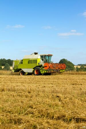 farm vehicle cutting the crops in summer Stock Photo - 15125490