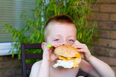 little boy eating a huge burger photo