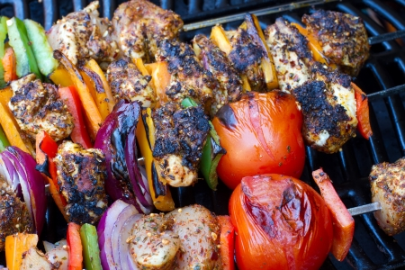 chicken and pepper kebabs slowly cooking on the barbecue photo