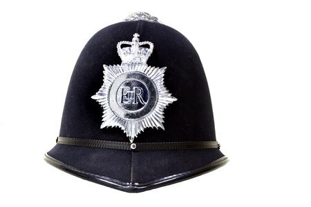 gorra polic�a: casco tradicional polic�a brit�nico aislado en blanco Foto de archivo