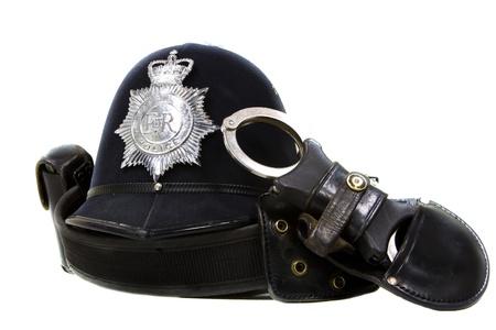 gorra polic�a: casco tradicional de la polic�a brit�nica y esposas aislado en blanco Foto de archivo