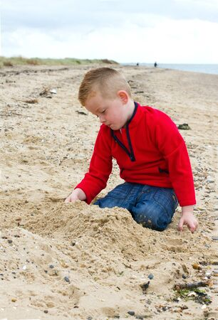 little boy playing on the beach in autumn photo