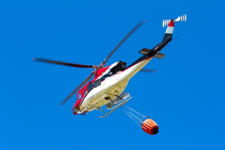 bush fire: emergency helicopter extinguishes flames of a raging bush fire