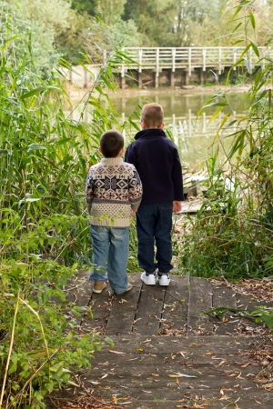 Brothers looking out across a pond in Autumn Stock Photo - 15945852