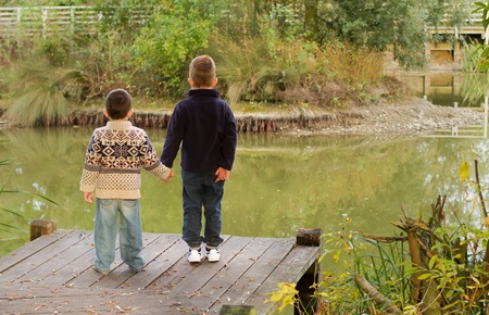 Brothers looking out across a pond in Autumn Stock Photo - 15945849