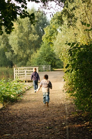 Brothers running near a pond in Autumn Stock Photo - 15945878
