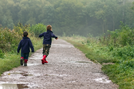 Two brothers splashing in puddles photo