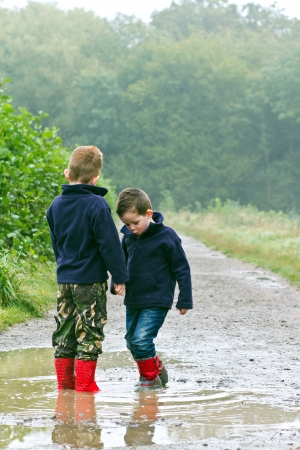 walking in the rain: Two brothers splashing in puddles Stock Photo