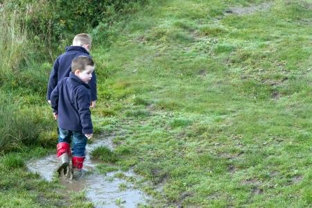 botas de lluvia: Dos hermanos chapoteando en los charcos