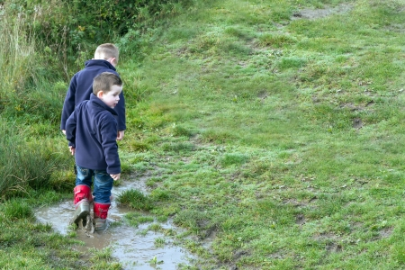 Two brothers splashing in puddles Stock Photo