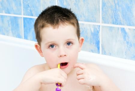 Little boy in the bath tub brushing teeth Stock Photo - 16803327
