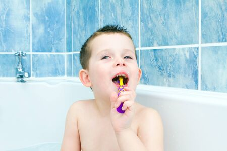 Little boy in the bath tub brushing teeth photo