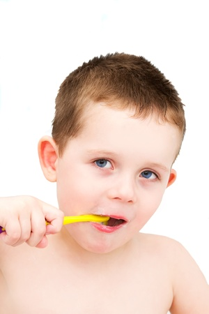 Little boy in the bath tub brushing teeth isolated photo