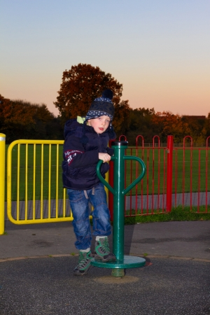 little boy playing on apparatus at the park photo