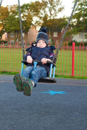 little boy on a swing at the park photo