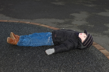 litte boy knocked down  outside on tarmac Stock Photo