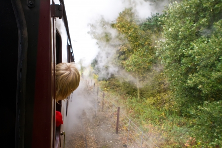 boy looking out through steam engine train window
