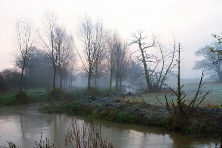 Misty river running through misty fields photo