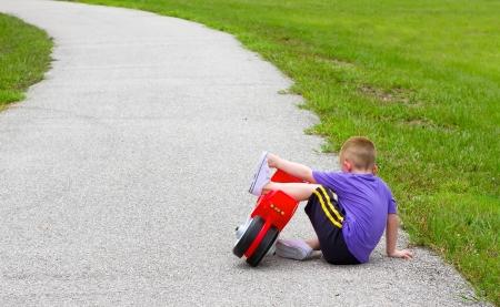 person falling: little boy fallen off of his bike
