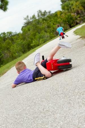 hombre cayendo: ni�o ca�do de su bicicleta Foto de archivo